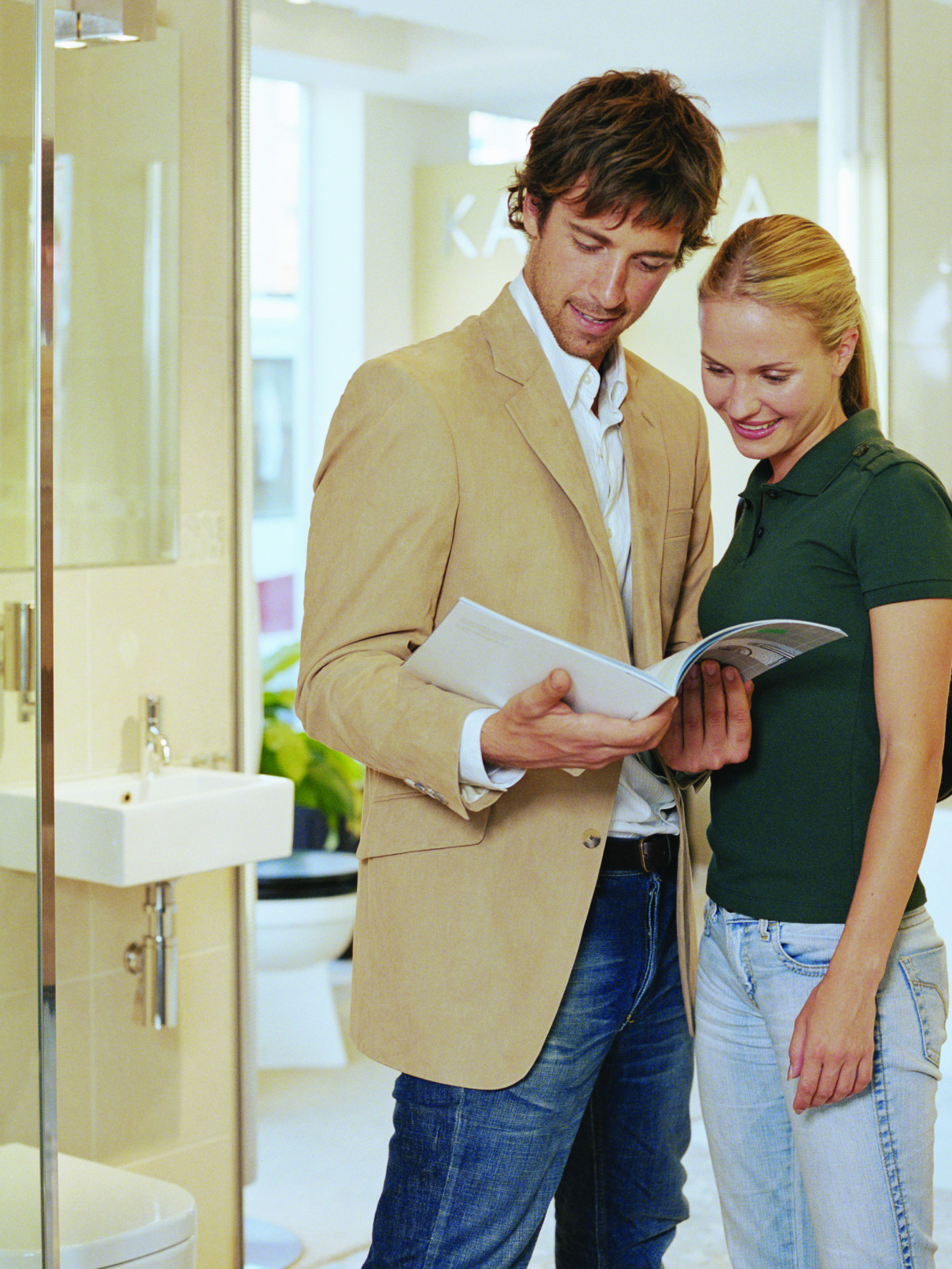 Couple looking at brochure in bathroom showroom, smiling